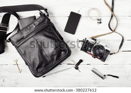 Objects on wooden background: leather bag, camera, smartphone, keys, flashlight. Outfit of urban traveler. - stock photo