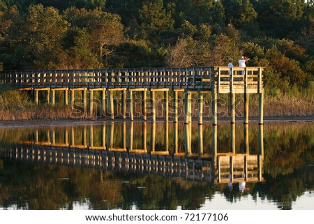 Observation deck at wildlife area. Late afternoon light, clear reflections in water. - stock photo