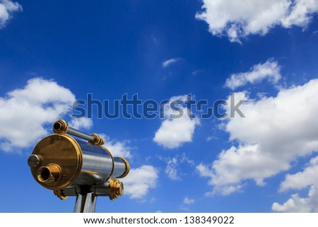 Observation telescope pointed to the beautiful blue summer sky - stock photo