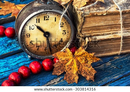Obsolete alarm clock on background of old books and yellow maple leaf.Photo tinted. - stock photo