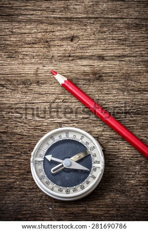 obsolete compass on wooden table top in retro style - stock photo