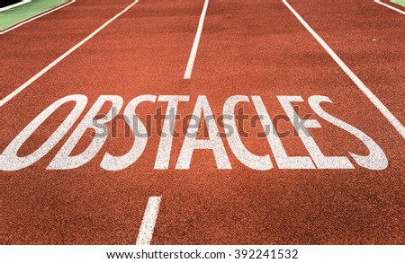 Obstacles written on running track - stock photo