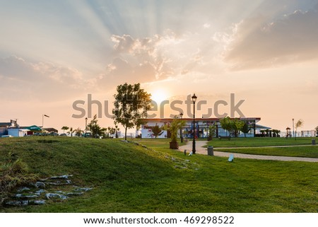 OBZOR, BULGARIA - AUG 01, 2016: Sunrise. The park near the sea in Obzor. Lawn, Hill with grass, a beach bar, lights. Picture taken during a trip to Bulgaria in the morning