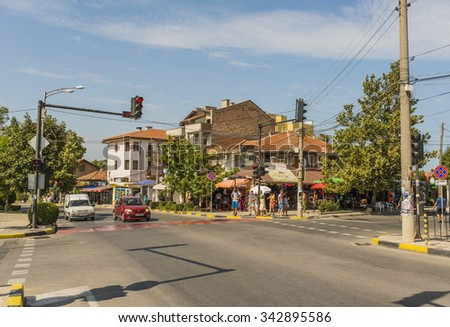 OBZOR, BULGARIA - AUG 09, 2015: Tourists walk during a summer vacation on sea.  Road intersection, shops, the road to the sea in the Bulgarian town of Obzor. Picture taken during a trip to Bulgaria