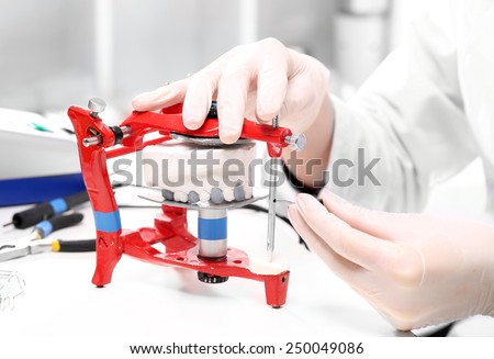 Occupation prosthetist. Prosthetics hands while working on the denture, false teeth, a study and a table with dental tools. - stock photo