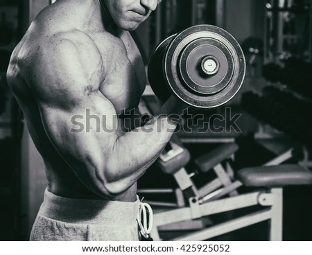 Occupation with dumbbells in the gym. Strong man with dumbbells - stock photo