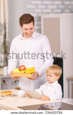 Occupied little guy. Dad watches his son using his digital notepad while holding a basketful of fruits.