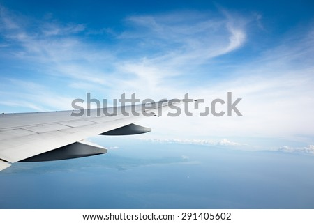 ocean and plane wing view from plane window - stock photo