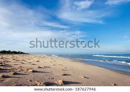 ocean and sandy beach on blue sky background - stock photo