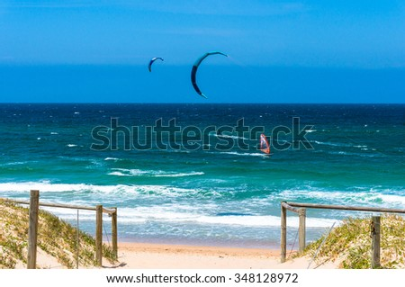 Ocean beach with kite surfers and windsurfers in a distance. Cronulla, Australia  - stock photo