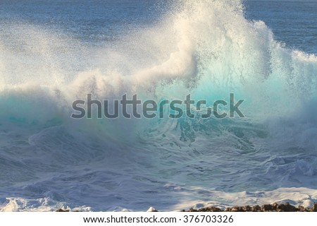 Ocean breaking surfing wave. Crashing foam in evening sunset light. Beautiful tropical oceanic background postcard. Big water splashes on seascapes. - stock photo