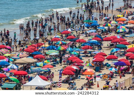 OCEAN CITY - JUNE 10: Beach full of people in Ocean City, MD on June 10, 2012 during OC Airshow. Ocean City, MD is a popular beach resorts on East Coast and one of the cleanest in the country. - stock photo