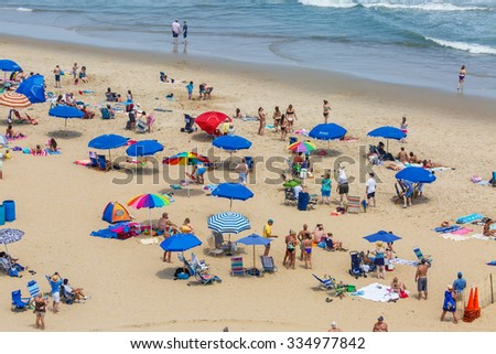 OCEAN CITY - JUNE 14: Tourists at the beach in Ocean City, MD on June 14, 2014. Ocean City, MD is a popular beach resort on the East Coast and it is one of the cleanest in the country. - stock photo