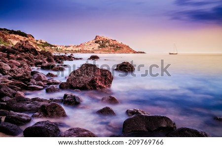 Ocean coastline with village in the background at sunrise, Castelsardo, Sardinia, Italy - stock photo
