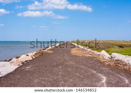 Ocean jetty walkway made of rocks and asphalt