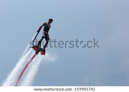 OCEAN MARINA, PATTAYA, THAILAND-NOV. 24: Unidentfied man demonstrates flyboard acrobatics, November 24, 2012 at the boat show in Ocean Marina, Pattaya, Thailand. - stock photo