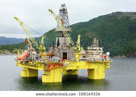 Ocean offshore oil rig drilling platform off near wooded shore of Stavanger, Norway. - stock photo