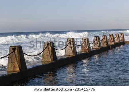 Ocean Pool Blocks Chains Tidal Pool ocean waves concrete blocks safety chains. - stock photo