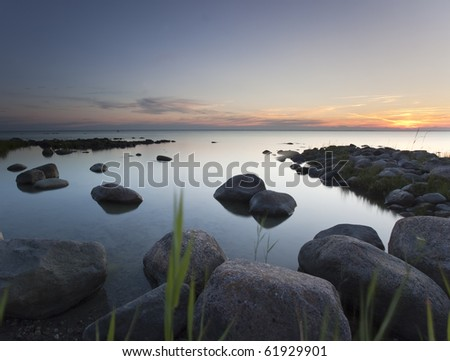 Ocean scene with windblown reed in the foreground - stock photo