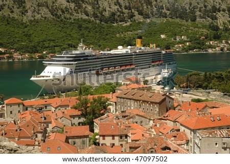 Ocean sea cruise ship in Mediterranean small city harbor - stock photo