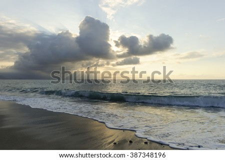 Ocean sun rays is brightly light golden seascape with waves rolling to the shore as scattered sunbeam break through a dramatically onto the ocean horizon. - stock photo