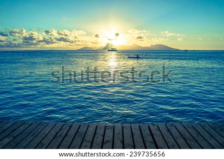 Ocean sunset from a wooden dock with kayak, sailboat, and mountain - stock photo