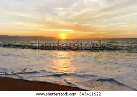 Ocean sunset is a beautiful ocean sunset with a soft wave rolling toward the sand and the orange sun setting in the cloud filled sky. - stock photo