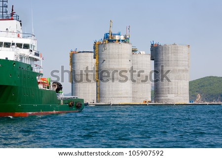 Ocean tug towing base offshore oil drilling platform. Sea of Japan. Russian coast. - stock photo