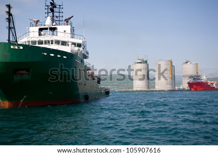 Ocean tugs at the base of offshore oil drilling platform. Sea Japan. Russian coast. - stock photo
