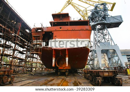 Ocean vessel under repair process in dry dock - stock photo