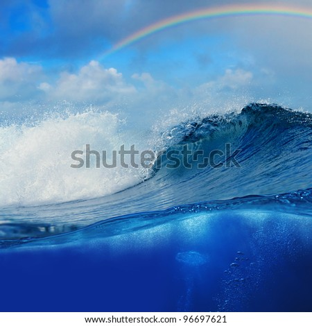 ocean view cloudy sky with colourful rainbow and breaking surfing wave splitted to two parts by waterline - stock photo