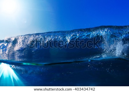 ocean-view seascape with blue sky and sunlight big curly ocean wave splitted by waterline to underwater part with air bubbles