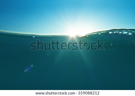 Ocean water design template with underwater part and sunset skylight splitted by waterline with air bubbles. - stock photo