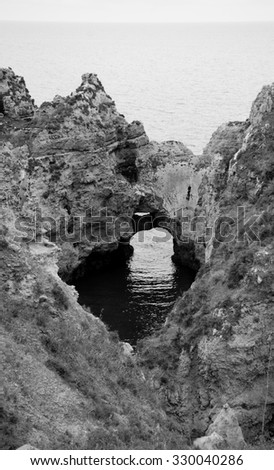 Ocean water seen through hole in rocks. Stone arches, caves, rock formations at Dona Ana Beach (Lagos, Algarve coast, Portugal) in the evening light. Aged photo. Black and white. - stock photo