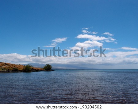 Ocean Waters and shoreline of the Kohala Coast at ancient Hawaiian historical site on the Big Island with Volcanic mountain in the distance with clouds hanging over it. - stock photo