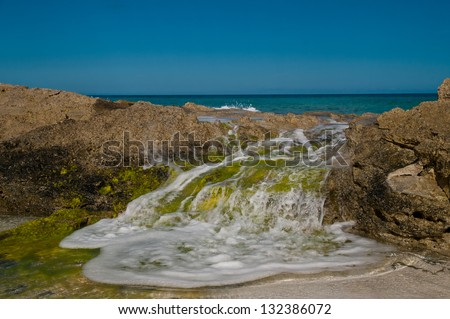 ocean wave rolling over rocks on a beach.  rocks are covered in gree algae and white foam in visible on the water.  copy space in the clear blue sky - stock photo