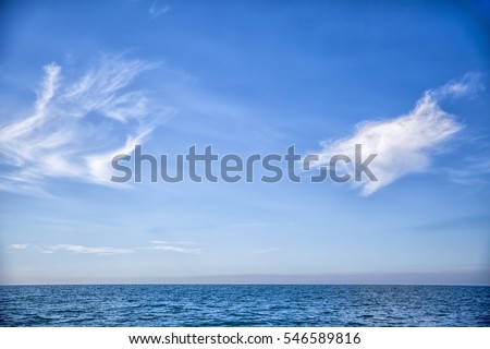 Ocean waves rolling on sunny blue sky day on horizon with light puffy white clouds while sailing on open water