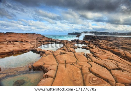 Ocean waves splash against spectacular rock formations at North Avoca, NSW Australia, with serene rockpools in the foreground.   - stock photo