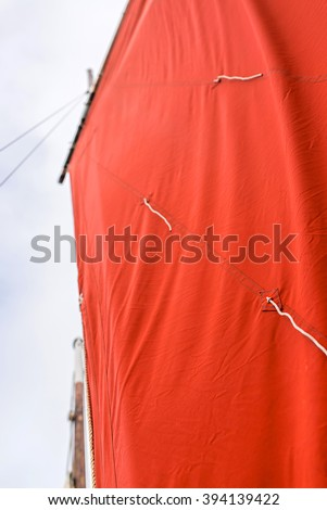 ocher sail filled by the wind on an old rigging sailing boat with a wooden hull and ropes, wooden mast and a yardarm during a sunny seat trip in brittany with a blur background - stock photo