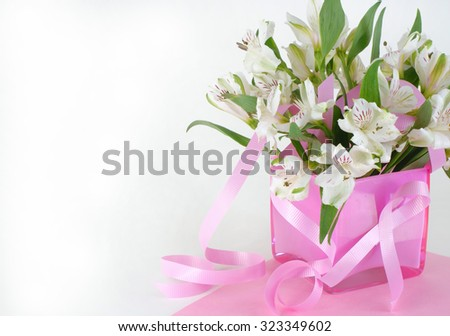 October is breast cancer awareness month. Image of white Peruvian lilies in a pink vase with a pink breast cancer awareness ribbon. Vertical composition with copy space