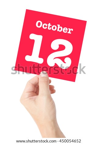 October 12 written on a card held by a hand - stock photo