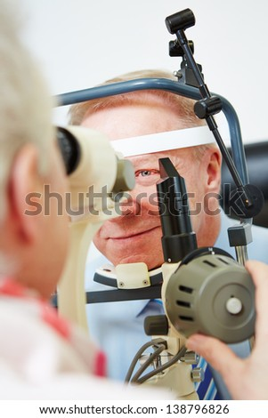 Oculist measuring cornea of elderly man with slit lamp - stock photo