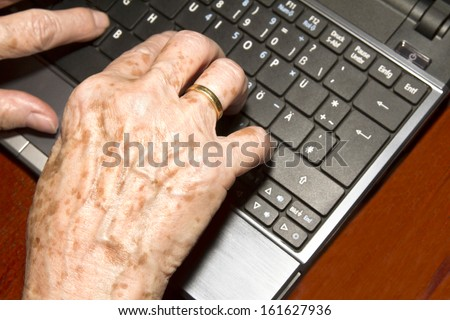 Od woman writes on a notebook - stock photo
