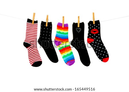 Odd socks whose mates have been lost, hanging on a clothesline.  Shot on white background. - stock photo