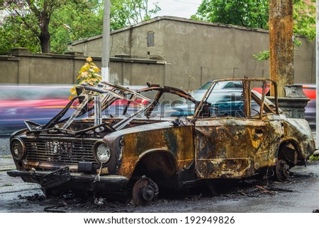ODESSA - MAY 14: Burned car on road with car traffic on a background on May 14, 2014 in Odessa, Ukraine. Abandoned car was exploded at night time on May 10, 2014. Long exposure shot. - stock photo