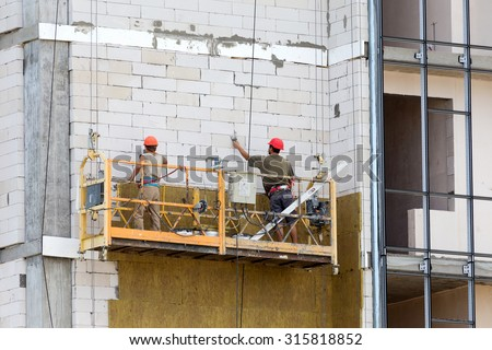 ODESSA - SEPTEMBER 8: facade thermal insulation works with stopping and fillers during the construction of high-rise apartment building September 8, 2015 in Odessa, Ukraine.