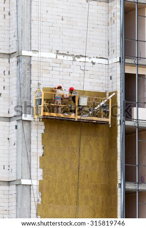 ODESSA - SEPTEMBER 8: facade thermal insulation works with stopping and fillers during the construction of high-rise apartment building September 8, 2015 in Odessa, Ukraine. - stock photo