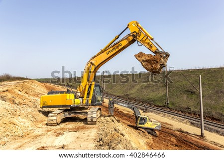 ODESSA, UKRAINE - April 7, 2016: Workers using heavy machinery repairing the railway line. Excavators, special technique on reconstruction of the railway rails