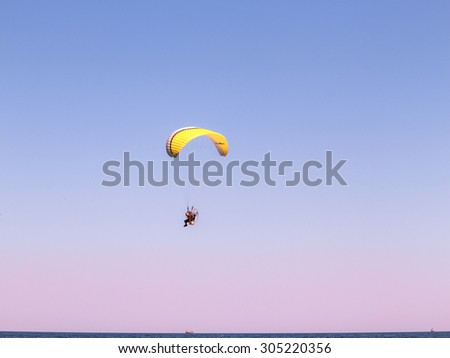 Odessa, Ukraine August 8, 2015: aredevil pilot with a motorized glider flying fast in the blue sky over the seaside with leisure travelers on the beach. airplane