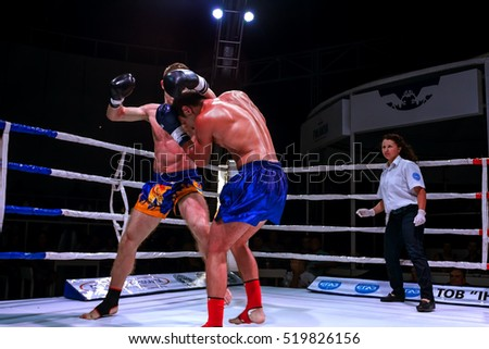 Odessa, Ukraine - August 18, 2013: Athletics MMA mixed martial arts fighters compete in cell, causing punches and kicks. Dramatic moment of ultimate fighting President's Cup. Boxers fighting in ring